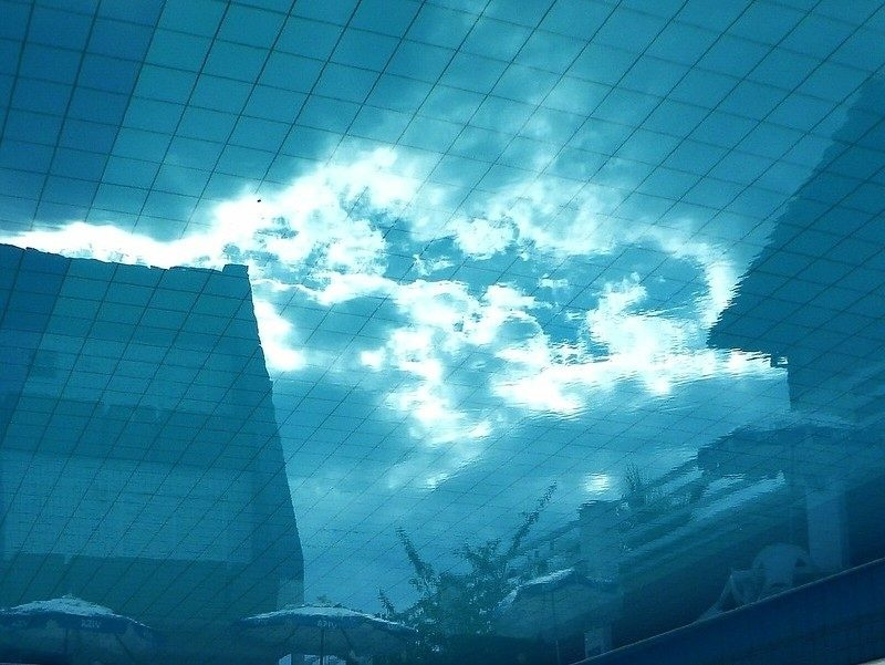 Picture of sky as if looking up from under water, with pool tiles reflected onto sky