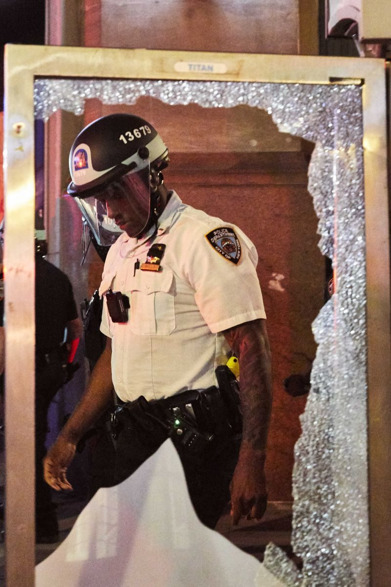 A police officer viewed through a shattered pane of glass