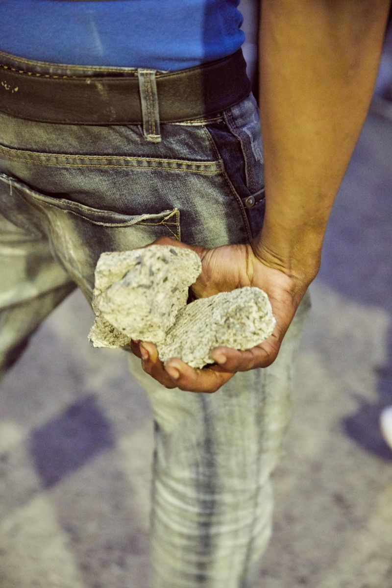 A person holds a handful of rocks behind his leg