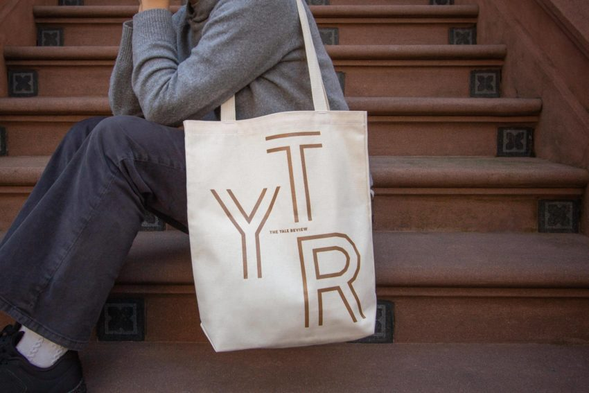A picture of The Yale Review tote bag on a person seated on brownstone steps.