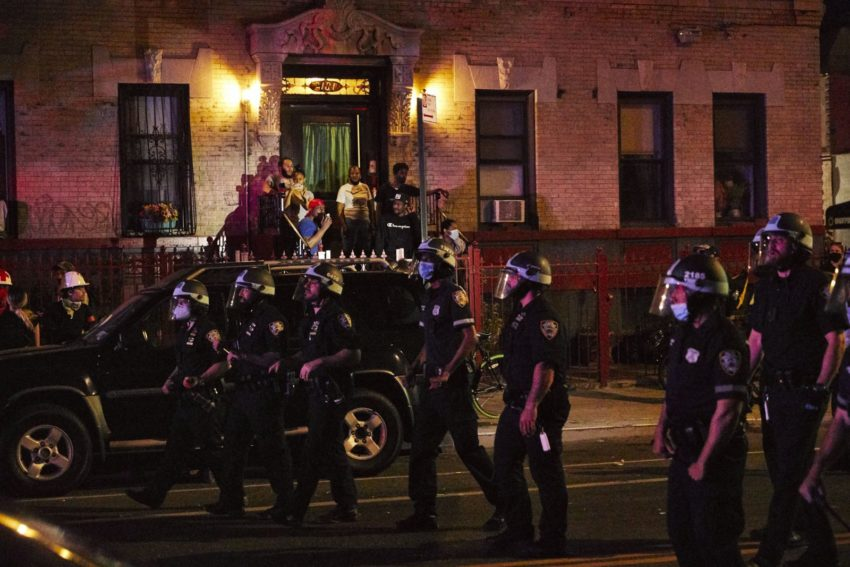 Civilians photograph a line of police officers marching down the street