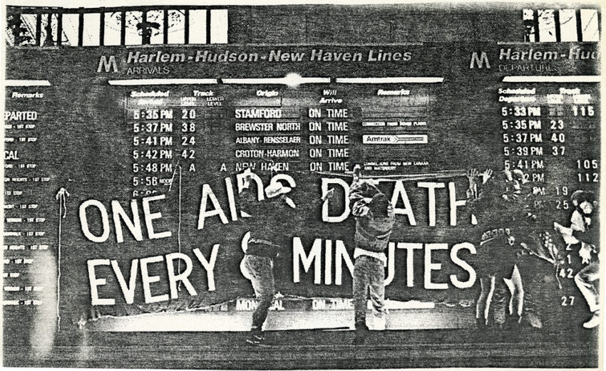 """ACT UP activists hang a banner in Grand Central Terminal, reading """"One AIDS death every 8 minutes."""""""