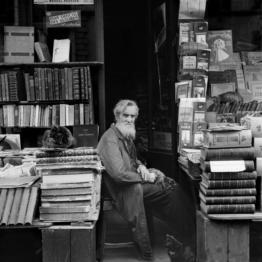 photo of man sitting amidst stacks and shelves of books