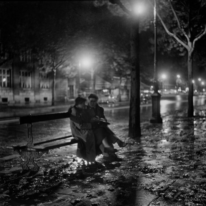 black and white photo of two people sitting together on a bench on a street late at night