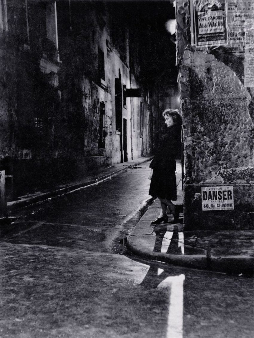 black and white photo of woman standing on street corner
