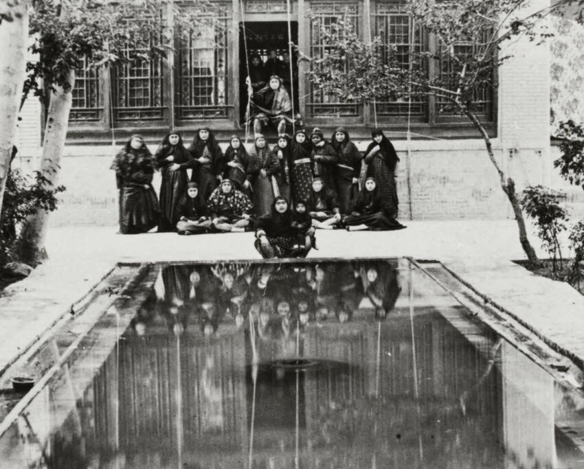 A group of people overlook a mirrored pool