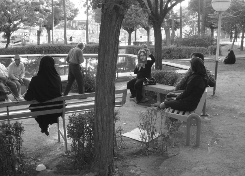 A group of people sit on chairs in a park