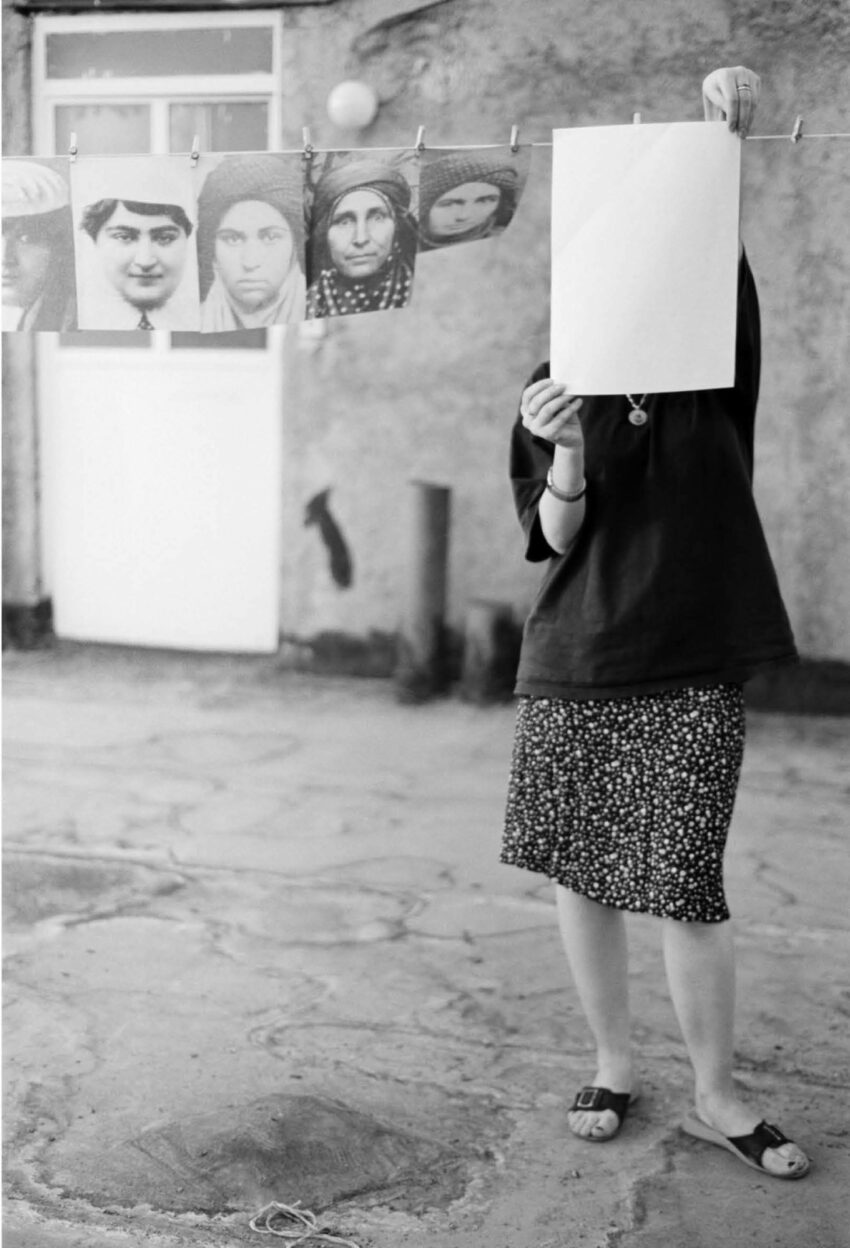 A woman holds up a paper to clip it to a drying line with other images
