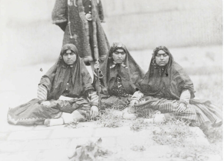 Three women sit in traditional garb, a fourth person standing behind them