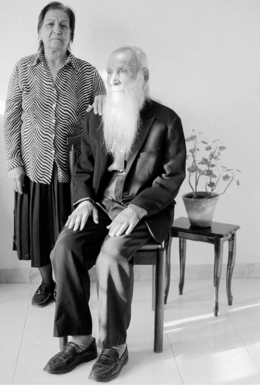 An older man and woman, the former sitting, the latter standing, with a potted plant
