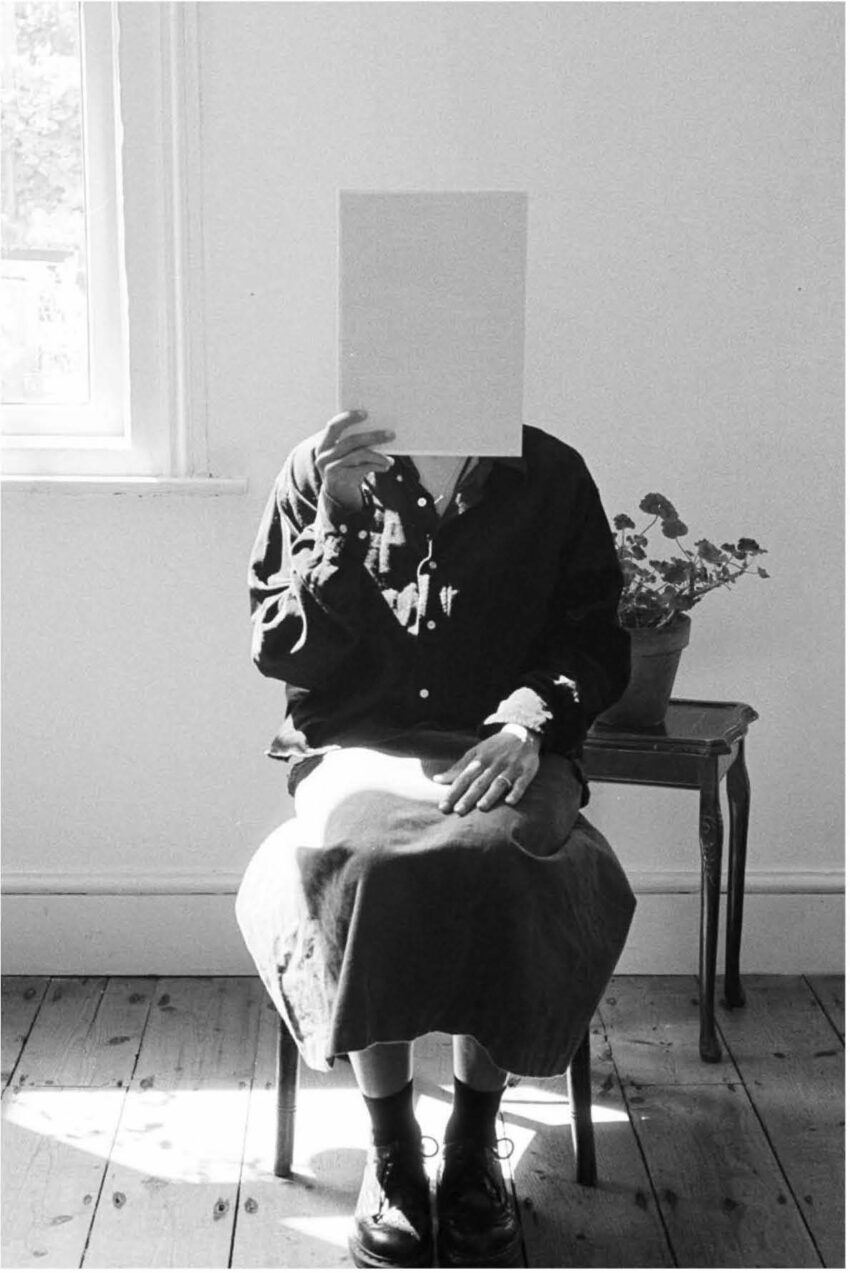 A woman sits before a potted plant, holding up a blank piece of paper which obscures her face