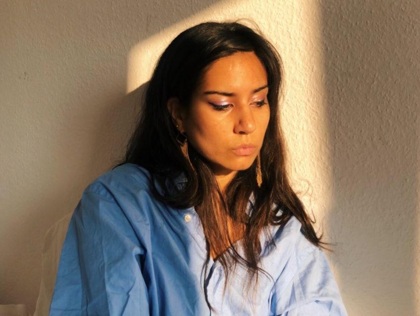 A portrait of poet Aria Aber in sunlight