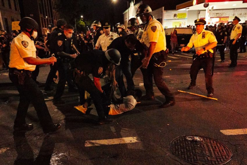 A group of police officers surround a man laying on the street