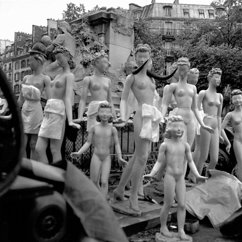 Mannequins posed in front of cemetery