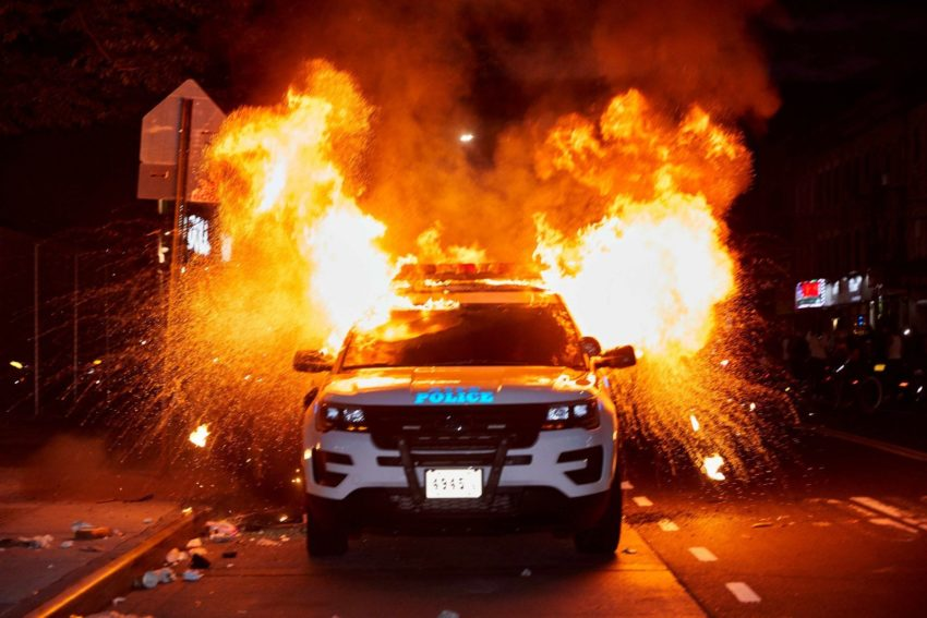 A police car with an explosion behind it
