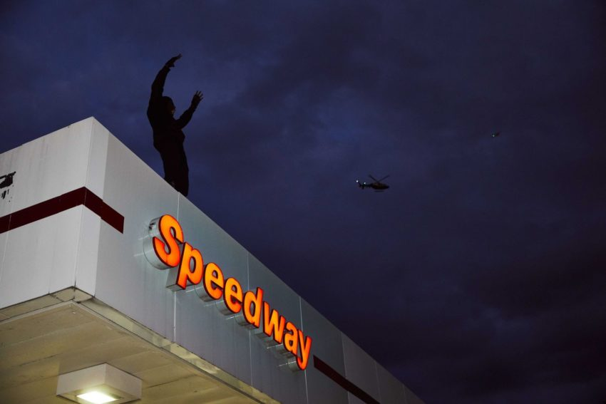 Silhouette of a man standing atop a Speedway gas station at night