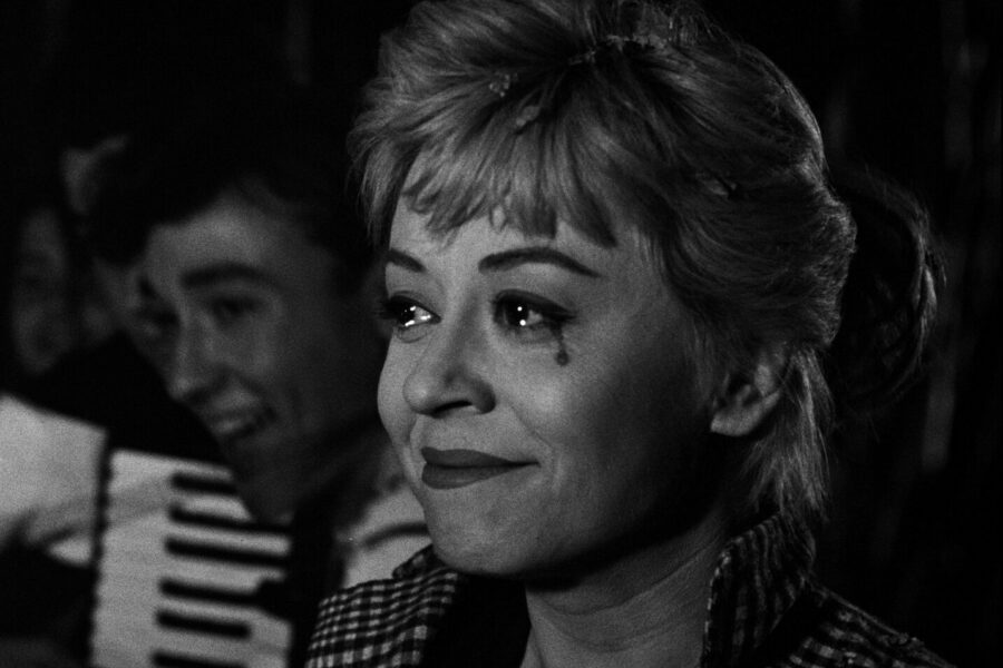 Black and white still showing Giulietta Masina smiling with a black tear at the corner of her eye
