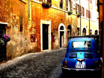 Cobblestone street with blue car and stone buildings. Mozzercork / Creative Commons