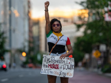 A Black woman raises her fist at a protest against police violence. Joyce by Miki J / Creative Commons