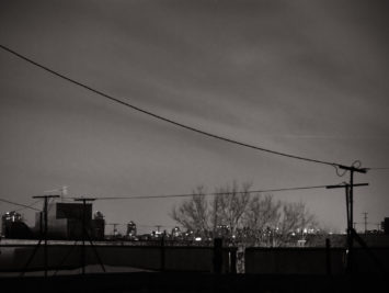 City skyline at night with a telephone wire in the foreground