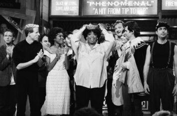Oprah Winfrey wears a tiara, standing with cast members of SNL
