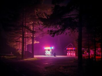 A gas station at night in the woods emanates pink light