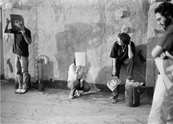 A group of people stand in various postures before a wall