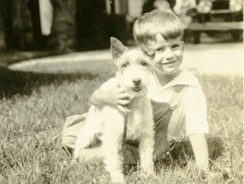 """Young James Merrill with his pet terrier at """"The Orchard"""" in 1930."""