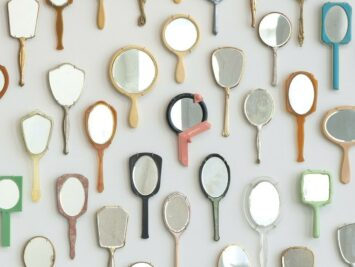 Installation of found hand mirrors arranged in an oval on a wall.