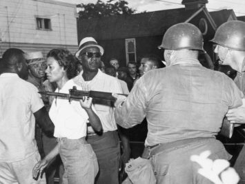The activist Gloria Richardson walking past National Guardsmen during a civil rights march in Cambridge