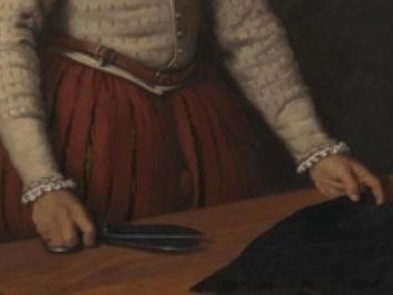 A tailor prepares fabric.