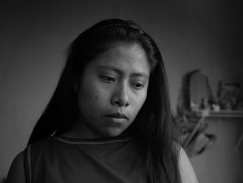 A woman looks down mournfully in a still from the film Roma.