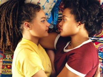 Two girls lie facing each other