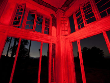 Corner of a windowed room with walls lit up red at night. Thomas Hawk / Creative Commons