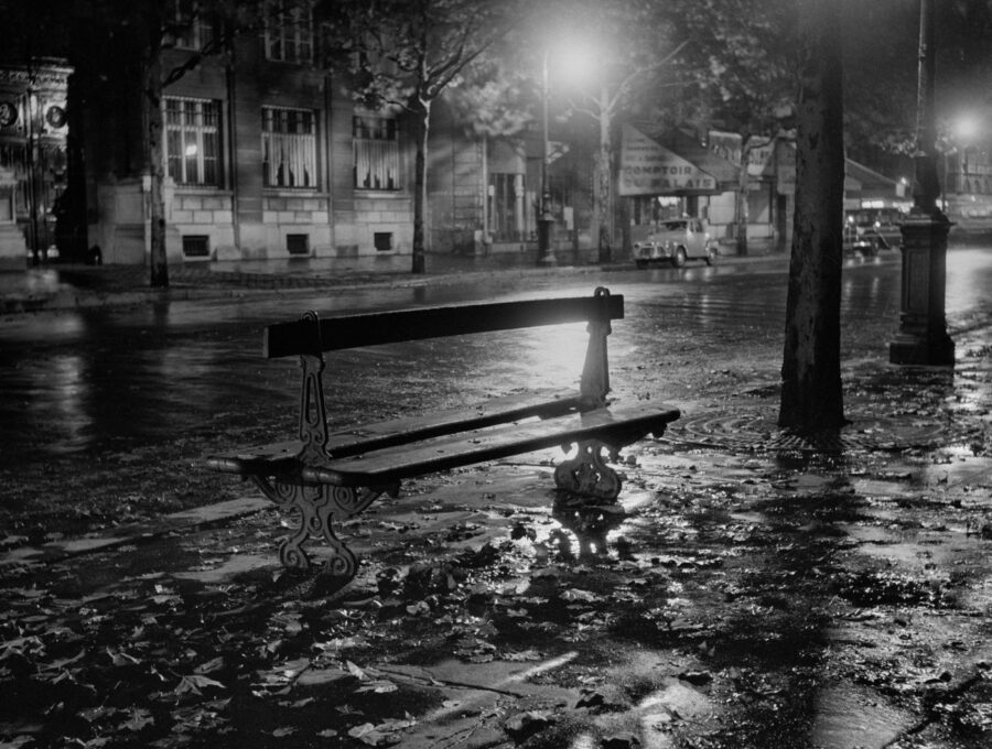 black and white photo of an empty bench on a street at night